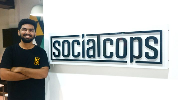 Siddharth in front of SocialCops sign
